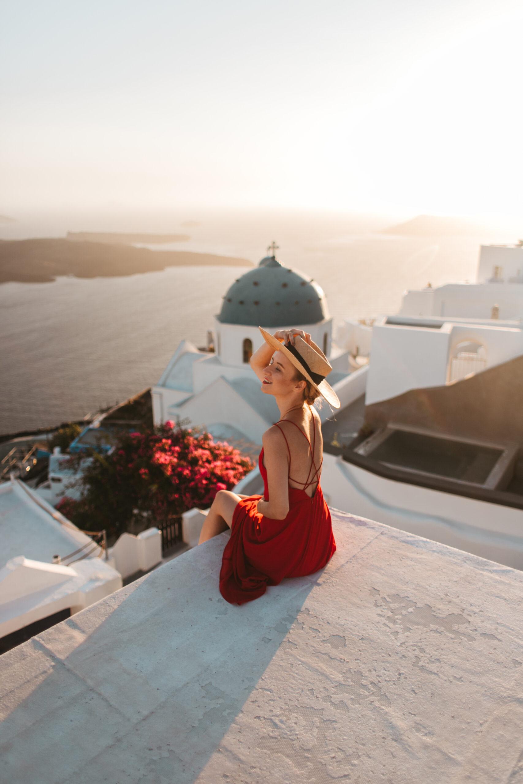 kobieta na dachu Santorini, białe domki, blog podrozniczy, blogerka, czerwona suknia, Imerovigli, Oia,